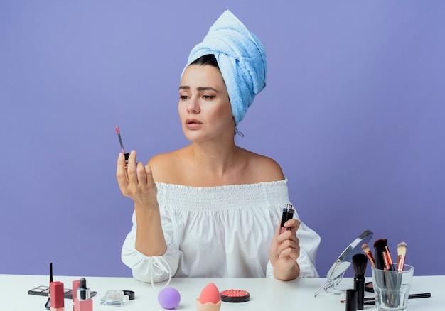 Belle fille bouleversée serviette de cheveux enveloppé se trouve à table avec des outils de maquillage tenant et regardant mascara isolé sur mur violet