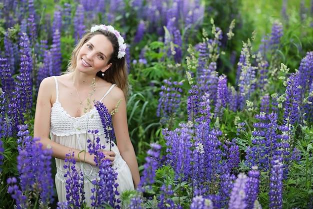 Belle fille avec un bouquet de fleurs bleues sur la nature en été