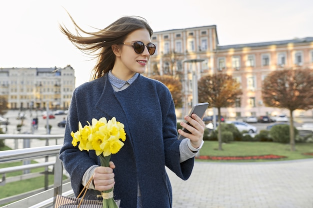 Belle fille avec bouquet de fleurs printanières jaunes