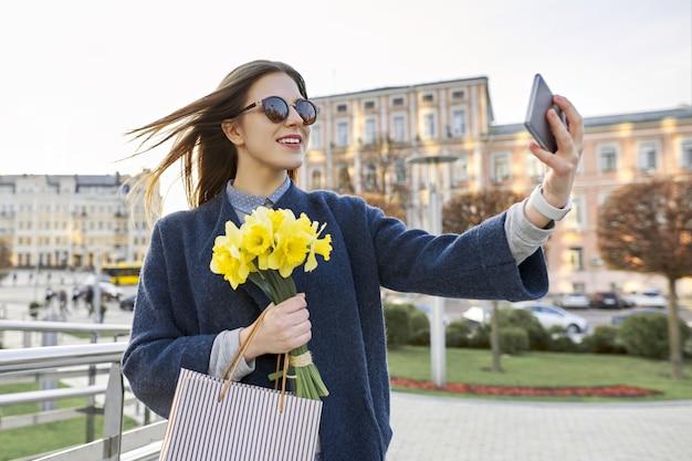 Belle fille avec bouquet de fleurs de printemps jaune