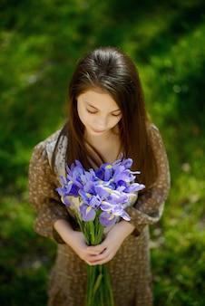 Belle fille avec un bouquet d'iris violet violet dans ses mains