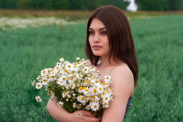 Belle fille avec un bouquet de marguerites dans un champ de fleurs.
