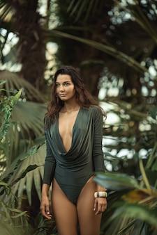 Une belle fille bronzée avec maquillage naturel et cheveux mouillés debout dans la jungle parmi les exotiques
