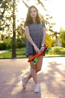Belle fille brune active aux cheveux longs portant un haut, un short en jean bleu et des baskets roses élégantes posant sur fond de coucher de soleil. fille tenant un patin orange avec des roues vertes.