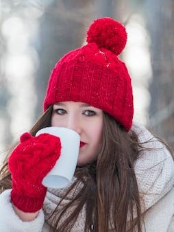 Belle fille brune au chapeau rouge et mitaines avec tasse de thé à l'extérieur. portrait de cadre vertical.