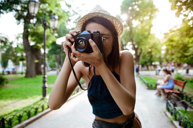 Belle fille brune au chapeau souriant, prenant des photos dans le parc.