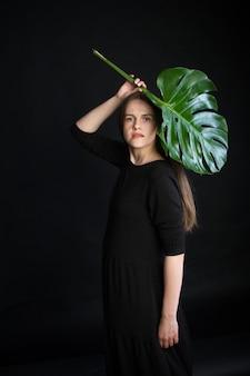 Belle fille brune aux cheveux longs avec une branche tropicale vert vif, fille avec feuille de monstera sur fond noir