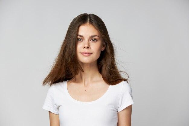 Une belle fille brune aux cheveux longs dans un tee-shirt blanc