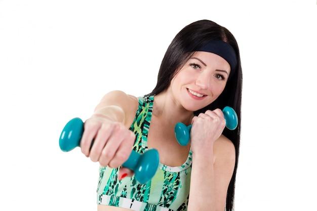 Belle fille brune aux cheveux longs est entraînée à la boxe avec des haltères bleus.
