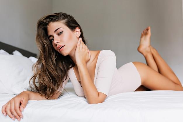 Belle fille brune aux cheveux longs portant sur le lit dans un appartement moderne. elle touche le cou et regarde.