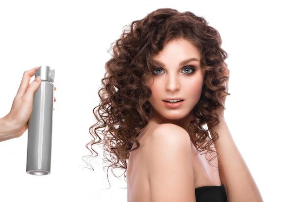Belle fille brune aux cheveux parfaitement bouclés avec vaporisateur et maquillage classique. beau visage.