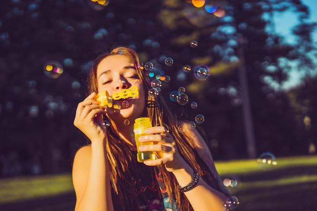 Belle fille brune aux longs cheveux bouffées de bulles de savon dans le parc