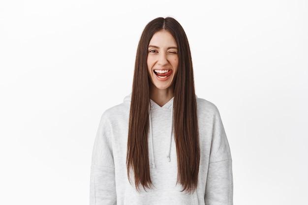 Belle fille brune aux longs cheveux raides, clignant de l'œil et montrant la langue, souriante des dents blanches parfaites, debout contre le mur du studio