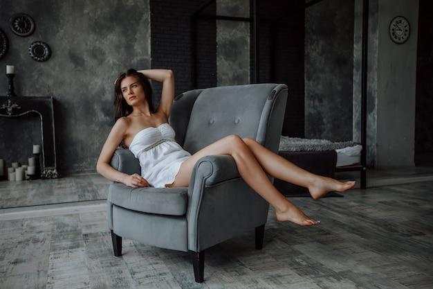 Belle fille brune aux longues jambes fines, assise sur une chaise sur fond sombre