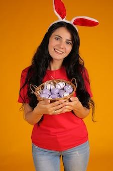 Belle fille brune aux oreilles de lapin rose tient un panier avec des oeufs de pâques fond jaune