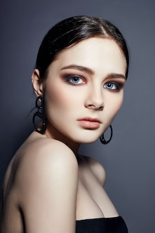 Belle fille brune avec des bijoux de grands yeux bleus