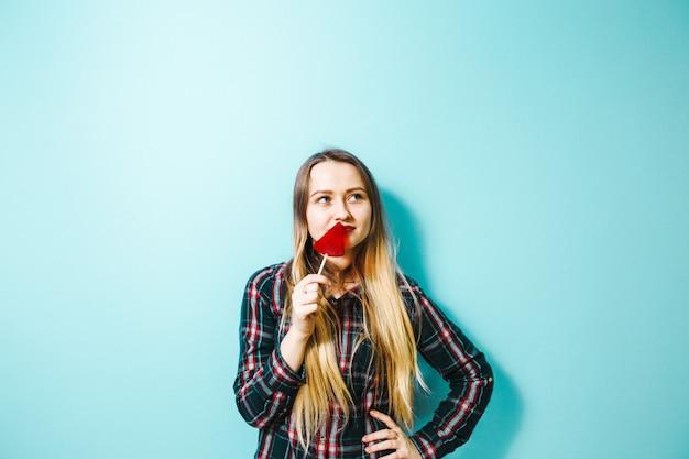 Une belle fille brune avec un bonbon à la main s'amusant sur un fond bleu.