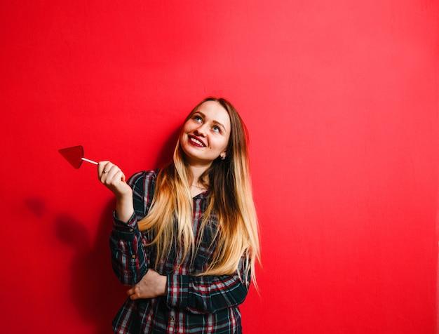 Une belle fille brune avec un bonbon à la main s'amusant sur un fond rouge.