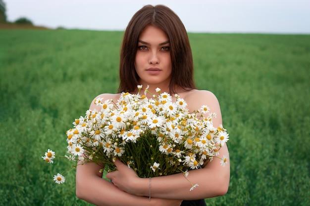 Belle fille brune avec un bouquet de fleurs de marguerites sur un champ avec des marguerites.
