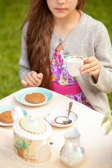 Belle fille brune buvant du thé à la terrasse du café