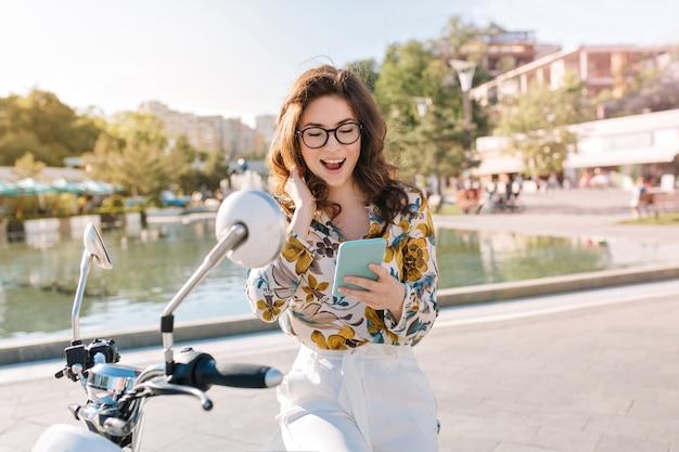 Belle fille brune avec une coiffure élégante vérifiant les réseaux sociaux tenant un téléphone mobile et souriant