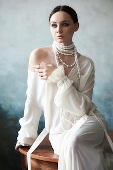 Belle fille brune élancée assise sur un canapé en robe longue blanche. portrait femme avec des bijoux sur le cou