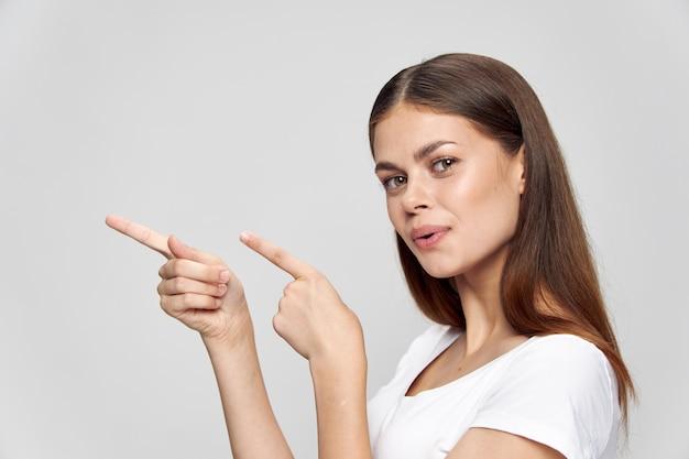 Belle fille brune sur un espace isolé montre ses doigts sur le côté copy space