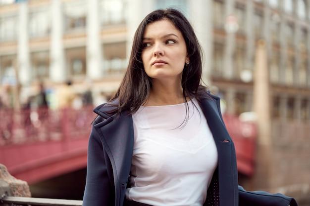 Belle fille brune intelligente grave se dresse sur le pont dans la rue de saint-pétersbourg