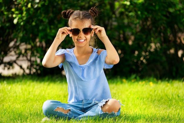 Belle fille brune à lunettes noires dans le parc assis sur l'herbe en été. photo de haute qualité
