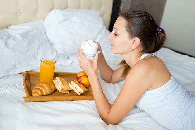 Belle fille brune manger le petit déjeuner et boire du café au lit