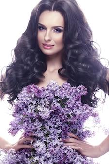 Belle fille brune avec un maquillage romantique doux, des lèvres roses et des fleurs. la beauté du visage.