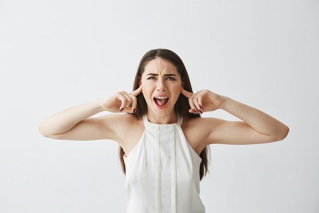 Belle fille brune mécontente fermant les oreilles avec les doigts de cris de bruit.