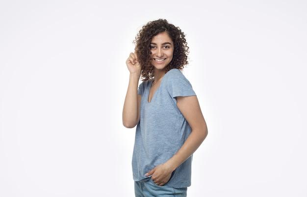 Une belle fille brune métisse heureuse détient une boucle de ses cheveux bouclés et sourit sur un fond blanc isolé.