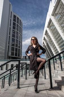 Belle fille brune à la mode dans une ville moderne