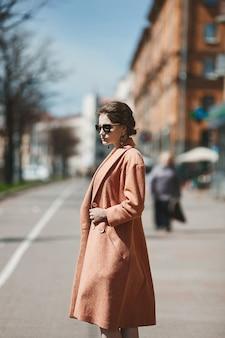 Belle fille brune modèle avec un manteau à la mode et des lunettes de soleil à la mode posant dans la rue de la ville