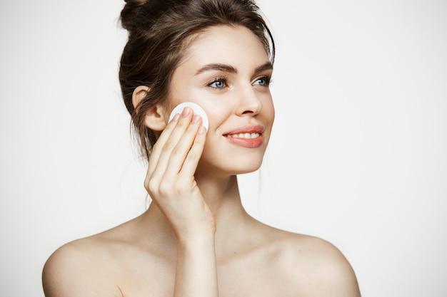 Belle fille brune naturelle, nettoyer le visage avec une éponge de coton souriant sur fond blanc. cosmétologie et spa.
