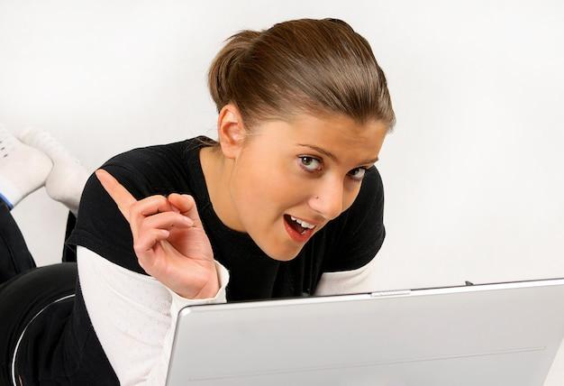 Belle fille brune avec un ordinateur portable allongé sur fond blanc