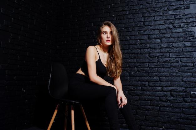 Belle fille brune porter sur fond noir, assis et posant sur une chaise au studio contre le mur de briques sombres.