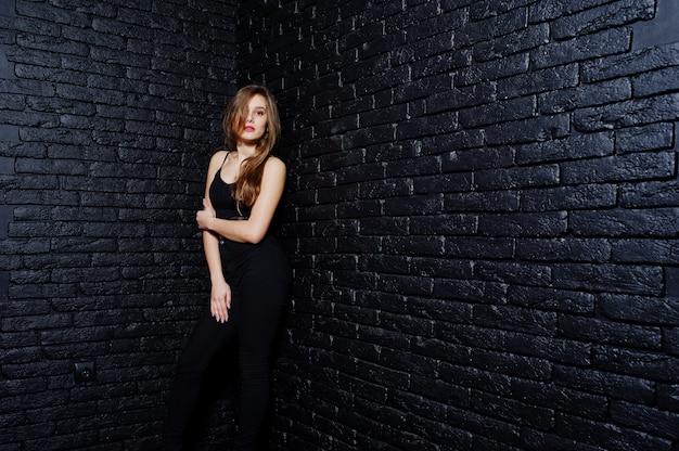Belle fille brune porter sur fond noir, posant au studio contre le mur de briques sombres.