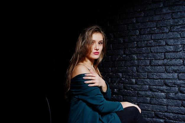 Belle fille brune porter sur une veste noire et verte, assis et posant sur une chaise au studio contre le mur de briques sombres.