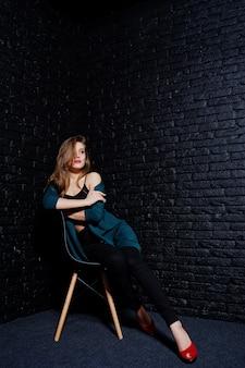 Belle fille brune porter sur une veste noire et verte en talons hauts rouges, assis et posant sur une chaise au studio contre le mur de briques sombres.