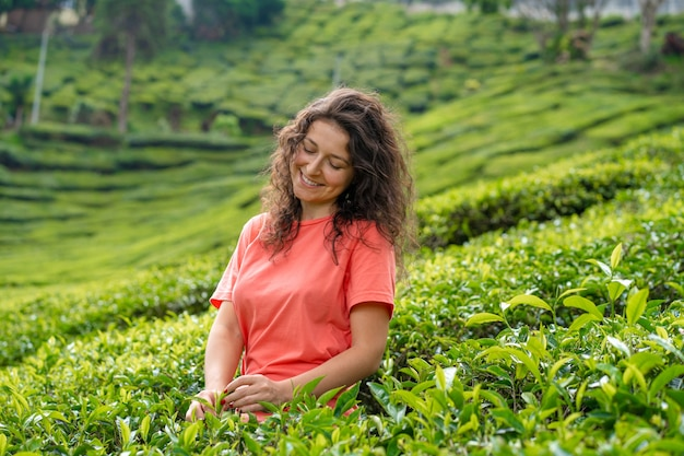 Belle fille brune posant au milieu de la vallée du thé entre les buissons de thé vert.