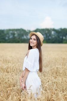 Belle fille brune en robe blanche et en chapeau de paille debout dans le champ de blé au coucher du soleil. récolte