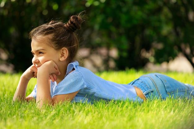 Belle fille brune se trouve sur l'herbe en été. photo de haute qualité