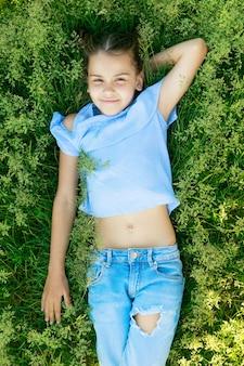 Belle fille brune se trouve sur l'herbe en été et sourit. photo de haute qualité
