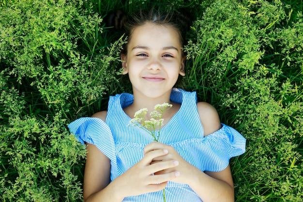 Belle fille brune se trouve sur l'herbe avec des fleurs en été et des sourires. photo de haute qualité