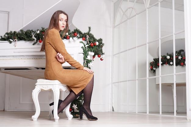 Belle fille brune sensuelle aux longs cheveux raides près d'un piano blanc avec décoration de noël
