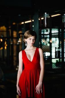 Belle fille brune sexy dans une robe rouge du soir debout près d'une fenêtre dans le café. regardant la caméra sérieusement.
