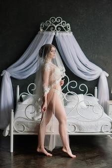Belle fille brune sexy en sous-vêtements blancs posant dans une pièce du studio intérieur