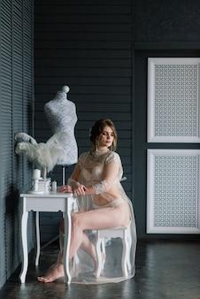 Belle fille brune sexy en sous-vêtements blancs posant dans une pièce à l'intérieur